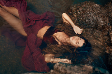 beautiful young woman in red dress lying down in water