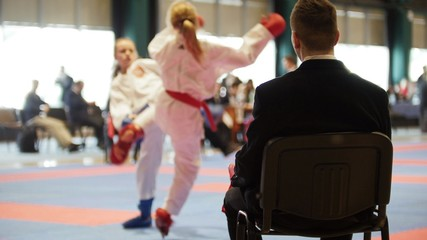 Martial art competitions - coach-judge at karate teenager's fighting