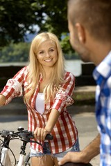 Happy casual blonde woman with bicycle outdoor
