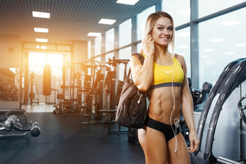 fitness sexy blonde girl with bag in gym smiling and relax after training