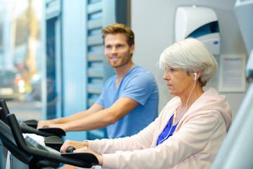young man and elderly lady using exercise machines