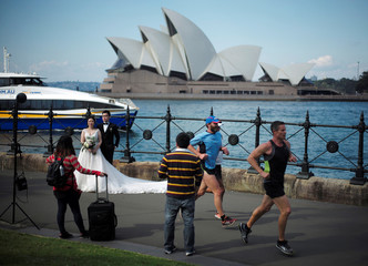 Lunchtime joggers pass through a harbourside photo shoot of a bride and groom in front of the Sydney Opera House in Australia