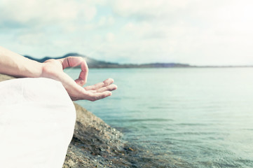 Hand of man meditating on a lotus pose on the beach