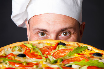 Portrait of happy attractive cook with a pizza