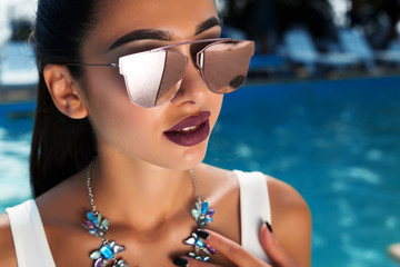 Summer fashion close up portrait of beautiful sexy woman in white stylish swimwear and mirrored sunglasses with perfect necklace and  hairstyle at swimming pool background
