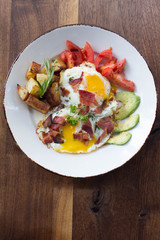Eggs over medium with a side of avocado, tomato, bacon, and potatoes