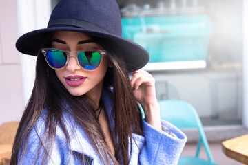 Lifestyle fashion close up portrait of young stylish hipster woman sitting in street cafe outdoor, wearing cute trendy outfit,smiling enjoy her weekends