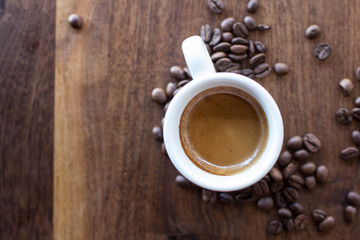 Freshly brewed espresso surrounded by coffee beans on a warm walnut wood table
