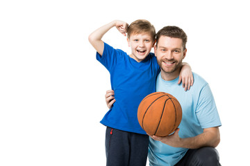 Smiling father and child ready to play basketball. Boy showing his biceps isolated on white