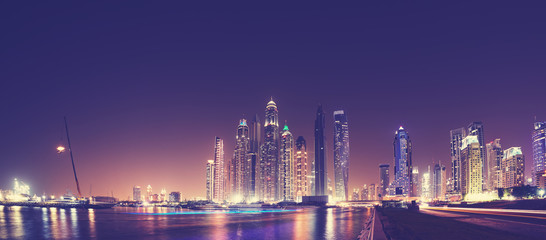 Fisheye lens panoramic picture of Dubai waterfront skyline at night, color toning applied, United Arab Emirates.