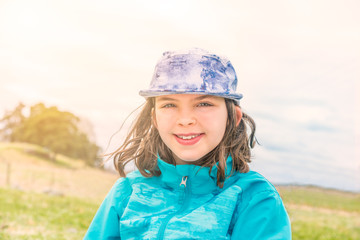Portrait of cute girl in blue jacket and cap with wind in her hair, outdoors in open landscape.