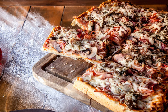 Rectangular ham and mushroom pizza served on wooden board