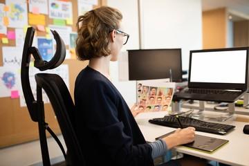 Businesswoman working on digitizer at desk