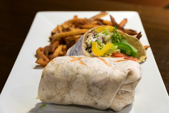 A Greek vegetarian wrap served with golden fries on a white plate.