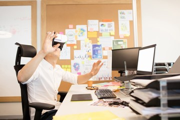 Creative designer gesturing while experiencing vr glasses