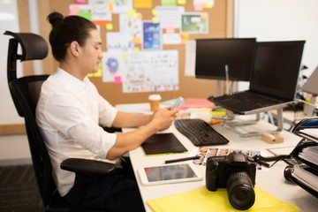 Designer using phone at creative office desk