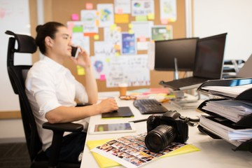 Designer talking on phone in creative office