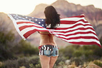 patriotic girl in bikini and sexy shorts holding american flag blowing in the wind