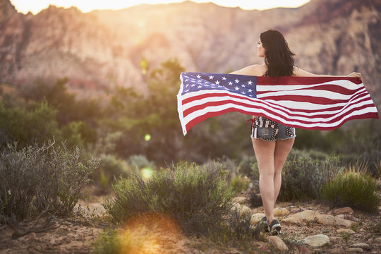 sexy girl standing with american flag in nevada desert at sunset