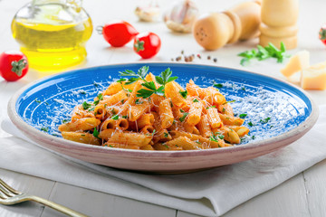 Traditional penne pasta with hot arrabiata tomato sauce and parsley on a white wooden table. Traditional Italian healthy food on a blue rustic plate. Close-up.