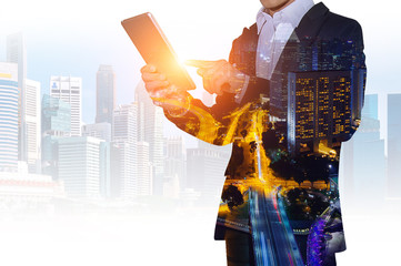 Double exposure of businessman holding tablet with cityscape blurred background, Business concept.