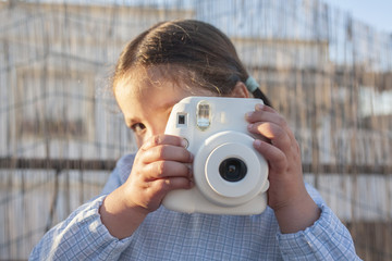Cute little happy girl with instant picture photo camera