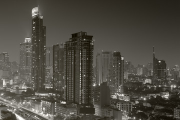 modern downtown night scene. hotel buildings, business towers, traffic lights. city travel monochromatic background. nighttime illuminated streets and metropolitan highway