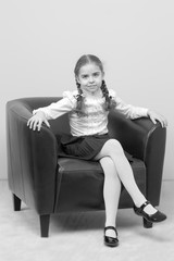 A little girl is sitting on a chair.