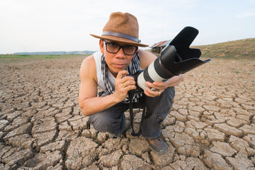 Photographer with zoom lens in dry land