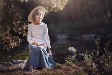 mujer mayor sentada en el campo
