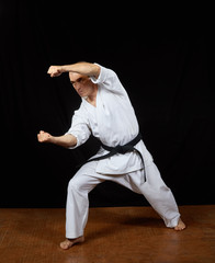 A man with a black belt beats two blow the hands Kaderov