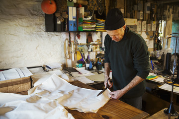 Man in a sailmaker's workshop cutting a piece of fabric for a sail.