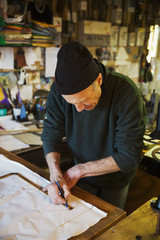 Man in a sailmaker's workshop measuring a piece of fabric for a sail.