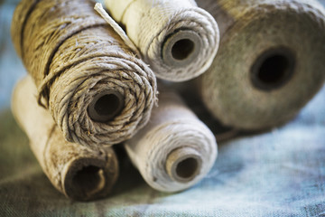 Close up of various bobbins of twine in a sailmaker's workshop.