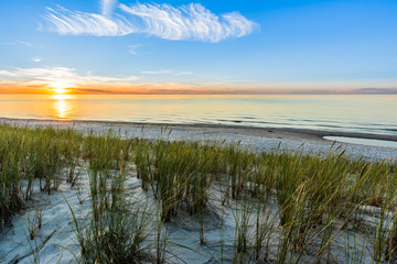 Sandy beach and sunset sky with golden sun shining on white sand