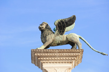 Close-up of column with the winged lion, symbol of Venice, and blue sunny sky in Piazza San Marco. At the city of Venice, the historic and amazing marine city.