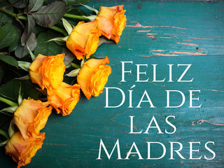 Mother's day card with Spanish words: Happy Mother's day, and orange roses on white wooden background