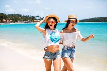 Two cute funny young hipster girls are walking along the beach, laughing, having fun, crazy emotions, wearing jeans shorts, white tops, straw hats, bright sunglasses, fashion accessories,  lifestyle