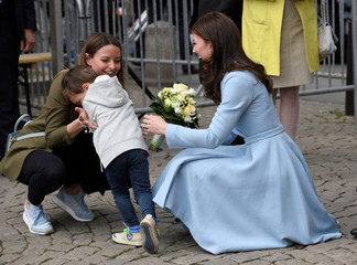 A young boy reacts after he handed a bouquet of flowers to Britain's Catherine, the Duchess of Cambridge in Luxembourg