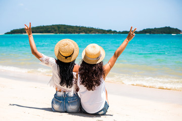 Two sexy young girls, best friends sitting together on white sand beach with the sun setting behind them with warm orange light, having fun .Wearing straw hat and sunglasses. Photographed from behind