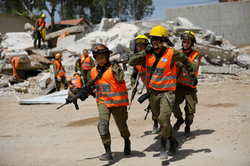 Joana Chris Arpon (front, L), an Israeli soldier from a search and rescue unit, whose parents immigrated from the Philippines, helps evacuate her comrade during a drill at Tzrifin military base