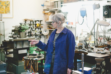 Senior female craftsperson pointing while working in jewelry workshop