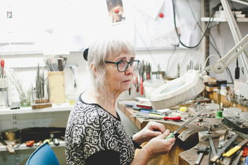 Senior craftsperson looking away while making jewelry in workshop