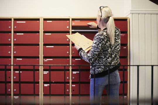 Rear view of teacher taking files from locker in school corridor