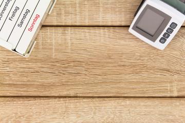 Tablettenspender und Blutdruckgerät auf holz hintergrund