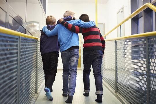 Full length rear view of boys walking arm around in school corridor
