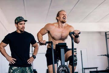 Bodybuilder spinning stationary bike in gym with personal trainer
