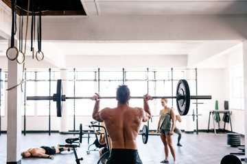 Rear view of man lifting barbell at gym
