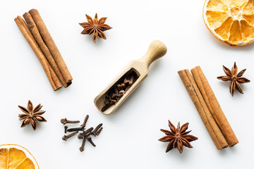 cloves with wooden scoop and cinnamon on white