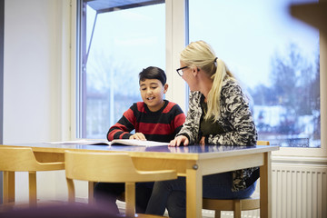 Mid adult teacher looking at boy reading book in classroom